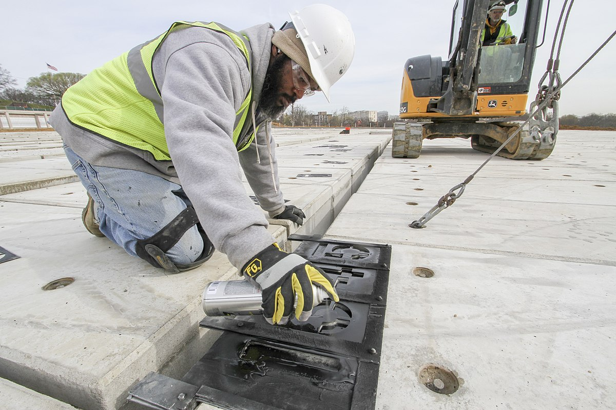Man spraying numbers on new concrete after repair.